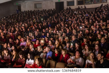 Odessa, Ukraine - April 12, 2019: Crowd of spectators at rock concert ALEKSEEV during music show. Crowds of happy people enjoy rock concert, raise their hands and clap their hands, audience on podium #1369684859