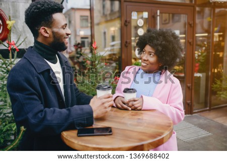 Cute black couple have fun in a city. Beautiful black girl in a pink coat. Man in a black coat. Couple with coffee #1369688402