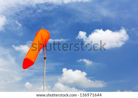 Airport windsock on the cloudy blue sky #136971644