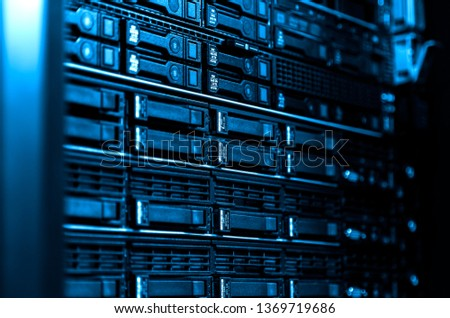 Close up blade server equipment rack in big data center with blurred side frame cold blue tone #1369719686