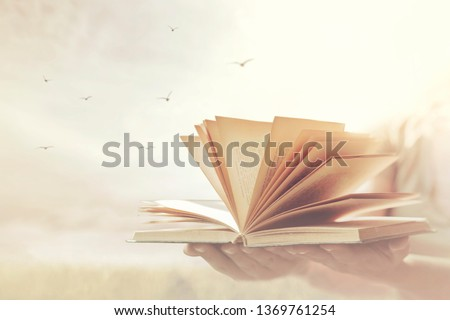 hands offer a book open to freedom and imagination #1369761254
