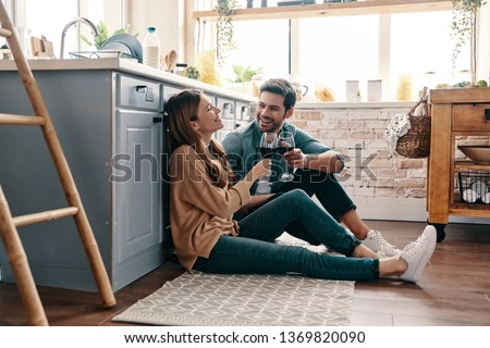 Love is in the air. Beautiful young couple drinking wine while sitting on the kitchen floor at home #1369820090