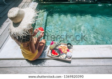 Girl relaxing and eating fruits in the pool on luxury villa in Bali. Exotic summer diet. Tropical beach lifestyle. #1369820390