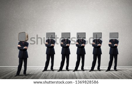 Businessmen in suits with laptops instead of their heads keeping arms crossed while standing in a row and one at the head with old TV in empty room against gray wall on background. #1369828586