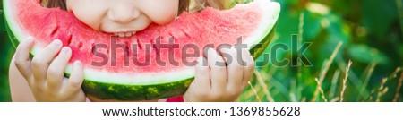 A child eats watermelon. Selective focus. Food nature
