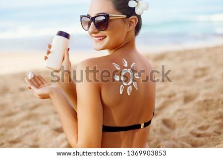 Woman apply Sun cream on tanned  back. Skin and Body Care. Sun protection. Portrait of Female in Bikini applying moisturizing sunscreen lotion and Sunblock. Girl Holding Suntan Lotion. #1369903853