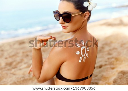 Woman Applying Sun Cream  on Tanned  Shoulder In Form Of The Sun. Sun Protection.Sun Cream. Skin and Body Care. Girl Using Sunscreen to Skin. Female Holding Suntan Lotion and Moisturizing #1369903856