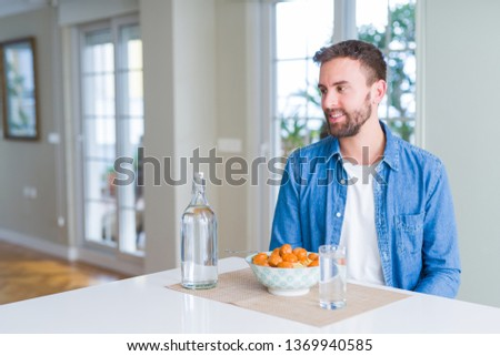 Handsome man eating pasta with meatballs and tomato sauce at home looking away to side with smile on face, natural expression. Laughing confident. #1369940585