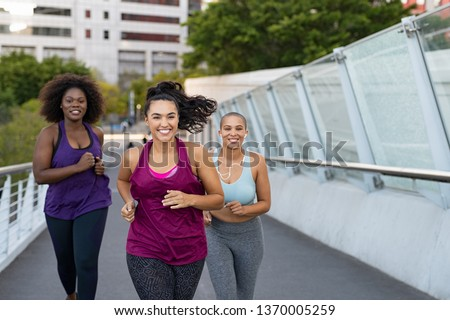 Happy young curvy women jogging together on city bridge. Healthy girls friends running on the city street to lose weight. Group of multiethnic oversize women running with building in the background. #1370005259