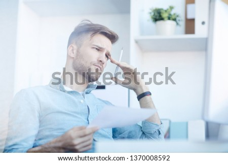 Side view portrait of handsome young man frowning in thought while working in office, copy space #1370008592