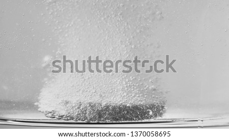 Macro Shot Of Effervescent Pill Dissolving In A Glass Of Water