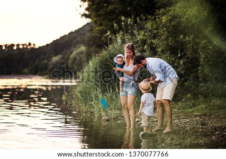 A young family with two toddler children outdoors by the river in summer. #1370077766