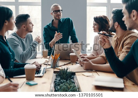 Planning new business strategy. Group of young modern people in smart casual wear discussing something while working in the creative office            #1370105501