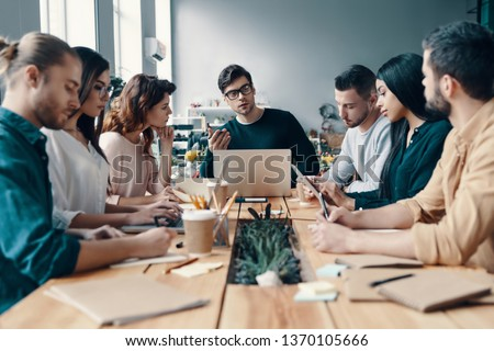 Leadership. Group of young modern people in smart casual wear discussing something while working in the creative office #1370105666