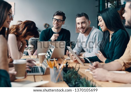 Putting ideas into something real. Group of young modern people in smart casual wear discussing something and smiling while working in the creative office #1370105699