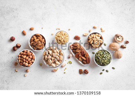 Various Nuts in  bowls on white background, top view, copy space. Nuts assortment - pecans, hazelnuts, walnuts, pistachios, almonds, pine nuts, peanuts, pumpkin seeds. Royalty-Free Stock Photo #1370109158