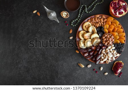 Traditional Muslim Iftar Food on black, copy space. Ramadan kareem with dates, nuts, dried fruits and coffee. Ramadan iftar food concept with rosary. #1370109224