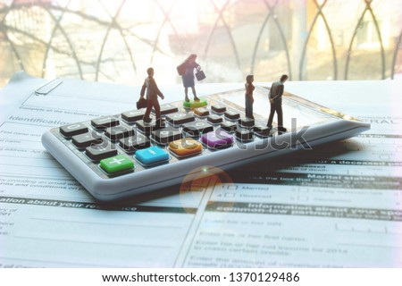 Miniature professional tax accountant or preparer on calculator. Blank tax forms ready to be filled out. Tiny team of men and women to help with your personal or small business taxes. Hire a pro. #1370129486