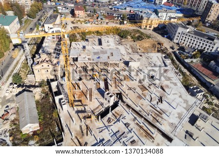 Construction site aerial view. Mall building base with solid concrete pillars. Heavy machinery and high tower crane working. Industrial aerial background #1370134088