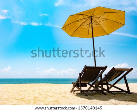 Beautiful scenery of two chairs and a white umbrella on the beach in summer. Copy area banner #1370140145