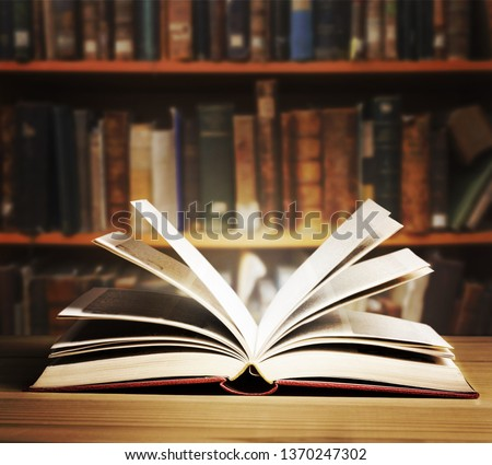 Old open book on a bookshelf background. #1370247302