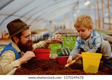 conditions of garden. father and son make good conditions of garden for planting trees. conditions of garden in modern greenhouse. conditions of garden concept. plants are their passion #1370249678