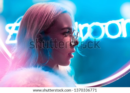 Young fashion teen girl in fur glasses looking forward illuminated with street neon blue pink sign, millennial woman with beautiful face in trendy night light glow back to 80s, profile side portrait #1370336771