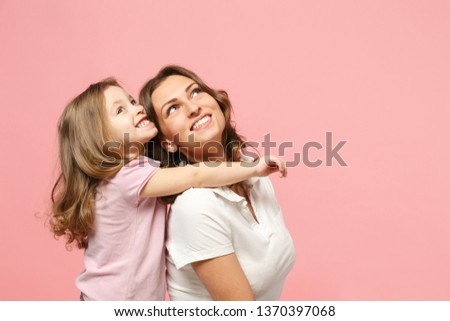 Woman in light clothes have fun with cute child baby girl. Mother, little kid daughter isolated on pastel pink wall background, studio portrait. Mother's Day love family, parenthood childhood concept #1370397068