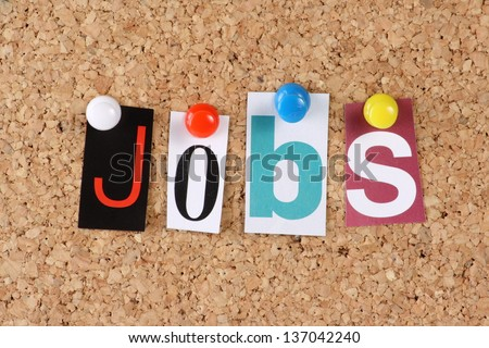 The word Jobs in cut out magazine letters pinned to a cork notice board Royalty-Free Stock Photo #137042240