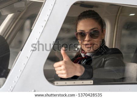Young Woman Pilot Looking Through The Cockpit Window and Giving Thumb Up. Portrait of attractive woman pilot with Sunglasses. She is looking at camera through  the cockpit window of a private plane. Royalty-Free Stock Photo #1370428535