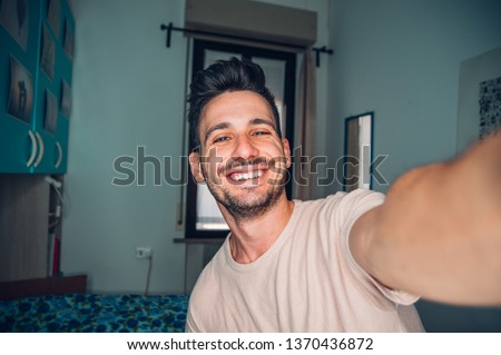 Handsome caucasian man taking a self portrait indoor at home #1370436872