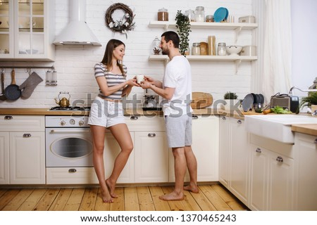 Happy couple woman and man making coffee with machine at their kitchen in new home. Having fun together and cooking breakfast. Happy young family concept #1370465243