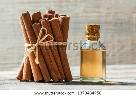 Close up bottle of cinnamon oil with cinnamon sticks and cinnamon powder on wooden background, healthy spice concept Cinnamomum verum  #1370484950