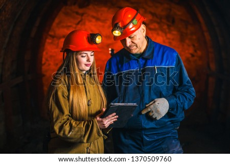 A beautiful young girl in a red helmet and with a electronic tablet in her hands is standing with a miner in a coal mine. Business plan discussion. #1370509760