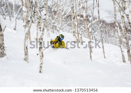 Man in yellow with backpack skiing steep hillside with many trees and soft powdery snow. The backcountry skier is on Niseko Mountain in Hokkaido, Japan. #1370513456