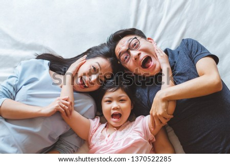 Happy Asian family laying on bed in bedroom with happy and smile, top view #1370522285