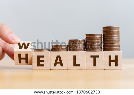 Hand flip wooden cube with word wealth to health with coins stack step up growing growth value. Investment in life insurance and healthcare concept Royalty-Free Stock Photo #1370602730