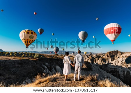 Wedding travel. Honeymoon trip. Couple in love among balloons. A guy proposes to a girl. Couple in love in Cappadocia. Couple in Turkey.  Man and woman traveling. Festival of balloons. Follow me #1370615117