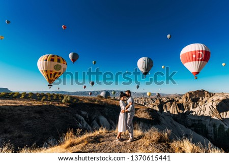 Wedding travel. Honeymoon trip. Couple in love among balloons. A guy proposes to a girl. Couple in love in Cappadocia. Couple in Turkey.  Man and woman traveling. Festival of balloons. Tourists #1370615441