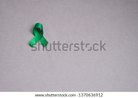 Green ribbon, symbol of kidney cancer. Cancer awareness month. Concept of health.  #1370636912