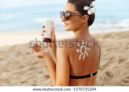 Facial Care. Young  Female Holding Bottle Sun Cream and  Applying on Face Smiling. Beauty Face.  Portrait Of Young Woman in hat Smear  Moisturizing Lotion on Skin. SkinCare #1370735204