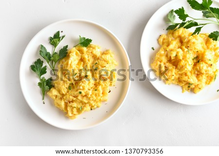 Scrambled eggs on plate over white stone background. Top view, flat lay Royalty-Free Stock Photo #1370793356