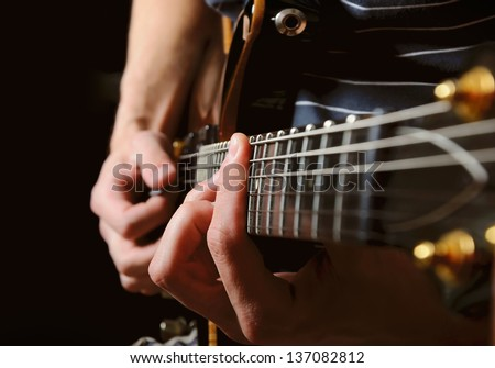 close up shot of strings and guitarist hands playing guitar over black - shallow DOF with focus on hands #137082812
