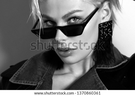 fashion photo of beautiful woman with short blond hair in elegant clothes with sunglasses posing in studio #1370860361