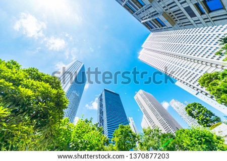 Asia Business concept for real estate, corporate construction and ecology - looking up view of panoramic modern city skyline with blue sky and green tree in shinjuku, tokyo, japan Royalty-Free Stock Photo #1370877203