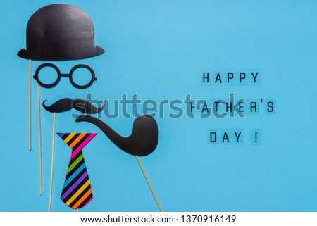 Various black photo booth props: cylinder hat, glasses, moustache, smoking pipe, tie on blue background. Greeting card, text HAPPY FATHER'S DAY. Creative composition in minimal style