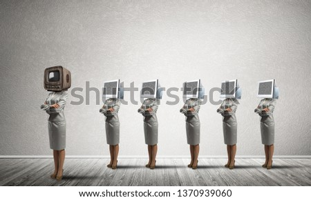 Business women in suits with monitors instead of their heads keeping arms crossed while standing in a row and one at the head with old TV in empty room against gray wall on background. #1370939060