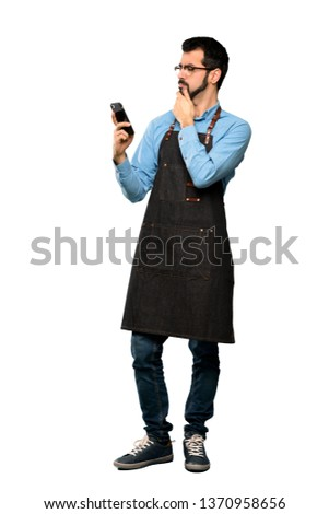 Full-length shot of Man with apron thinking and sending a message over isolated white background #1370958656