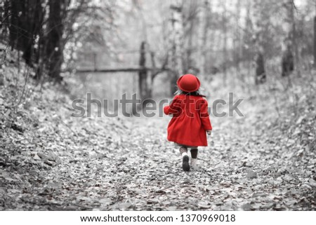 A girl in a red coat and felt hat walks merrily through the autumn forest, golden autumn, childhood and loneliness, selective color