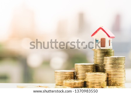 Concept for property ladder, mortgage and real estate investment. House models on top of coins pile with city backgrounds. #1370983550